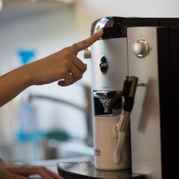 Finder drückt auf Knopf von Kaffeemaschine